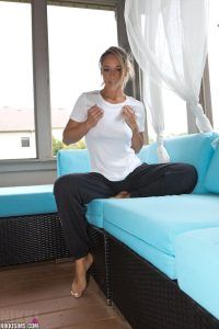 Nikki Sims relaxing on her stylish blue sofa in her white top and black tracksuit bottoms