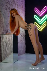 Naked cutie bending over and showing off her stylish tattoo and sexy ass